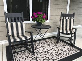 Four black front porch chairs with 2 outdoor rugs