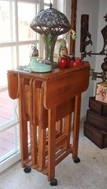 Wood tray tables stored in drop leaf high table on wheels. Tiffany style lamp, blue dial phone
