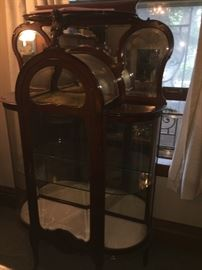 Antique Curved beveled glass Curio Cabinet in Excellent condition.  This one is a truly beautiful piece with unique details carved in a rich mahogany.