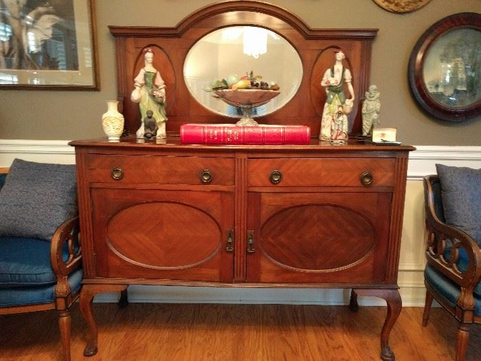 """Lovely 1930's mahogany sideboard, with matched veneers, topped by a pair of vintage Cybis figurines, and a huge Holbein book """"The Queens Collection at Windsor Castle""""."""