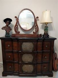 Marble-topped 3-drawer chest, with vintage chalk figure hussy and jade lamp.                                                Vintage swivel shaving mirror on chest.