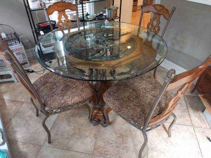 Lovely breakfast table with extra heavy beveled glass top and four heavy iron/wood side chairs.