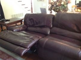 Showing one of the seats reclined on the leather couches.