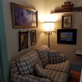 Plaid loveseat, and framed wall decor