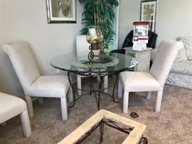 Contemporary glass topped dining table and four chairs.