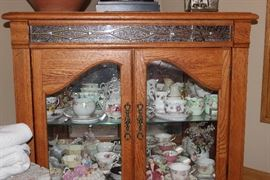oak china cabinet filled with china