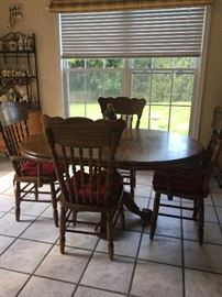 Hardwood kitchen table with claw foot base and four chairs.  Remove extender for round table.