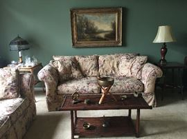 Bamboo table, lamps, couch and loveseat, lots of brass knick-knacks.