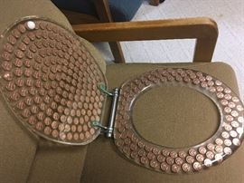 Pennies in lucite commode/toilet seat.  Standard round.