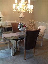 Glass over Brass dining table with 3 sets of matched pairs of chairs priced separately.