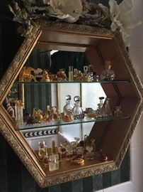 "Gold curio glass shelf cabinet with Este Lauder ""collectores"" perfume bottle collection"