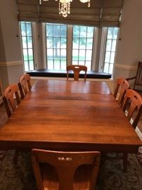 Beautiful solid oak table with three leaves, that comfortably seats 10 people and can be extended to accomodate 20+ people.  6 matching chairs + 2 Captain chairs...