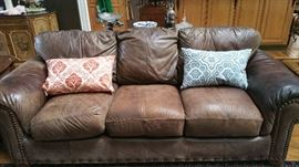 Large oversized chocolate brown leather sofa with nail head trim.