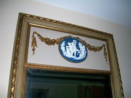 Wedgwood applique at the top of a mirror.