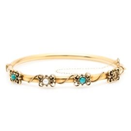 14K Yellow Gold Turquoise and Cultured Pearl Cuff Bracelet: A 14K yellow gold cuff bracelet showcasing two round cabochon turquoise and one round bead cultured pearl set into openwork scrolling motifs accented by a rope like design.