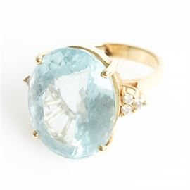 14K Yellow Gold, 17.65 CTS Aquamarine, and Diamond Cocktail Ring: A 14K yellow gold cocktail ring featuring one center 17.65 cts faceted oval cut aquamarine flanked by round brilliant cut diamond side stones.