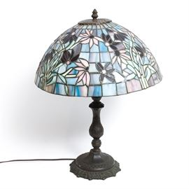 Tiffany-Inspired Table Lamp: A Tiffany-inspired table lamp. This lamp features a stained glass shade with a floral motif expressed in hues of blue and purple. It has a curved column and an ornately decorated base. This lamp is unmarked. It is tested and operable.