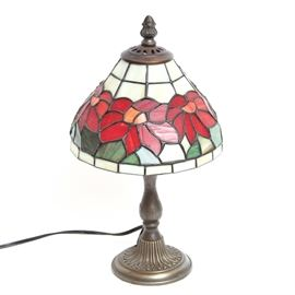 Tiffany-Inspired Table Lamp: A Tiffany-inspired table lamp. This lamp features a stained glass shade with a red floral motif. It has a curved column and rests on a round base with a flower petal decoration. Item is tested and operable. Unmarked.