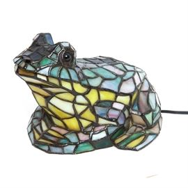 Stained Glass Frog Lamp: A stained glass frog lamp. This forgot shaped lamp is made of metal with stained glass panels in colors of green, purple, yellow, pink, and red. The piece is unmarked.