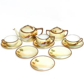 """Vintage Handpainted Nippon Tea Set: A vintage handpainted Nippon tea set. This porcelain set features a waterfront scene with palm trees and a building. The collection includes a tea pot, cream, double handle lidded sugar bowl, two cups and six saucers. They are marked, """"Handpainted Nippon"""" to the bottom."""