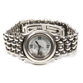 """Chopard """"Happy Sport"""" Diamond Wristwatch: A Chopard diamond wristwatch. The silver tone metal watch has a heavy bracelet with a fold-over clasp and round, white dial with black Roman numerals, and five diamonds. The top of the case has three colored glass cabochons in bezel settings."""