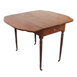 Antique Cherry Pembroke Style Table: An antique cherry Pembroke style table. This table features a rectangular top, with a pair of scalloped drop panel sides, above a pair of pull out drawer ends and panel apron sides. The drawers include a knob pull and both have hand cut dovetail joinery. The table rises up on turned, tapering and reeded legs including bobbin turnings and ending in casters.
