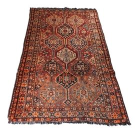 Hand-Knotted Tribal Kazak Area Rug: A hand-knotted tribal Kazak area rug. The wool area rug features Memling guls with poles connecting to each gul with small floral accents in colors of navy, onyx, blue, tan, white, and brown upon a red field. Surrounding the field are guard borders of styles in barber poles and a diamond-box pattern that supports the main border, having multicolored octograms with natural fringe to both ends. It is unmarked.