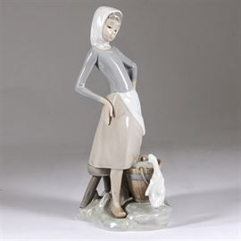 """Lladró """"Girl With Milk Pail"""" Figurine: A Lladró figurine titled Girl With Milk Pail"""". This work depicts a young girl in a light blue dotted scarf and white apron standing up from her milking chores and looking down at a white goose, which is peering in the full pail of milk. The piece was first introduced in 1970 and was modeled by Vicente Martínez. It was retired in 1990. The figure is executed in Lladró's signature palette of cool pastel tones and is marked to the base """"Lladró – Hand Made in Spain""""."""