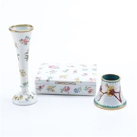 Enameled and Cloisonne Decor: A small grouping of enameled and cloisonne decorative pieces. This grouping offers three pieces including a cloisonne toothpick holder, with floral motifs against a white background. There is also a white enameled bud vase and matching trinket box, with applied floral decals. The trinket box offers a hinged lid, and wooden interior, they both go with out markings.