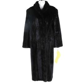 """PD Furs Full Length Black Mink Coat: A PD furs full-length black ranch mink fur coat. This coat has a wrap around style with a high rolled collar and hook and loop closure front. Other features include long sleeves, side besom pockets, and a black lining. Interior has a monogram that reads """"Sandra Fossick"""". The label reads """"Pd Furs""""."""