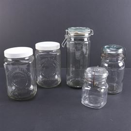 """Vintage Glass Canisters: A collection of five vintage and newer glass jars. There are two pieces with white lids and molded type reading """"Golden Harvest"""" The remaining vintage examples include jars by Atlas and Ball together with an octagonal jar with a rubber sealing ring."""