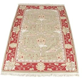 Handwoven Kilim Area Rug: A handwoven kilim area rug. This cotton rug features a rectilinear floral pattern with large floral pendants in a palette of cochineal red, olive taupe, peach and cream. The primary border offers stylized palmettes on meandering vines. The rug is finished with overcast edges and a cotton warp fringe at either end. Unlabeled.