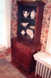 Small antique walnut wall cupboard and vintage stoneware.