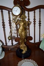 Gilded iron lady, with swinging pendulum clock