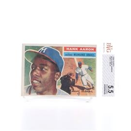 """1956 Topps Hank Aaron Card: A 1956 Topps Hank Aaron card. The card is marked """"outfield Milwaukee Braves"""" and features the printed signature in cursive """"Henry Aaron"""". The sleeve is marked BVG Beckett"""", """"#31A Hank Aaron – Grey Back"""" and """"5.5 Excellent"""". The back of the card features statistics and color illustrations."""