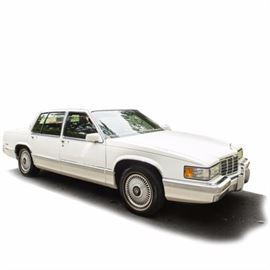 1992 Cadillac Sedan de Ville: A white full size 1992 4-door Cadillac Sedan de Ville; VIN is 1G6CD53B9N4315202 and with 91,475 miles. Features include an automatic transmission, a 4.9 liter V8 gasoline engine, a vibrant red leather interior, power windows, locks, and more. The original owner's manual along with Cadillac owner's items are also included.