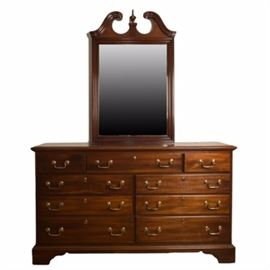 """Georgian Manor"" Dresser with Mirror by Dixie Furniture: A vintage cherry dresser with mirror by Dixie Furniture for Lexington Furniture. The piece is part of their ""Georgian Manor"" collection and features Chippendale styling. This set includes a rectangular top dresser with beveled edge over nine drawers that feature dovetail construction and is adorned with brass tone bail handles and escutcheons. The piece rests on ogee bracket feet. The rectangular mirror features a wooden frame with broken scroll and a central finial. The piece is marked ""Dixie"" to an interior top drawer. Please see items 17CLT104-070 and 17CLT104-071 for coordinating pieces."