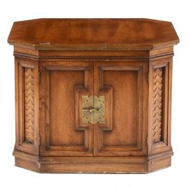 Vintage Octagonal Accent Table: A vintage accent table, in walnut with a warm finish. It has an octagonal top with a carved border to the edge and carved designs to the front corner panels. The base has a cabinet space enclosed by double doors, secured with a brass latch. The piece sits on a plinth base. It is in a matching style with 17CIN440-163 and -164.
