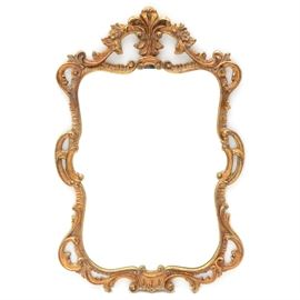 Rococo Style Wall Mirror with Gold Tone Frame: A circa mid- to late 20th century vintage Rococo style wall mirror. It has a carved wood frame with foliate motifs and a gold tone metallic finish with black thread accents. There is a metal wire to the reverse for hanging, and the piece is unmarked.