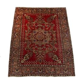 Semi-Antique Persian Hand-Knotted Tabatabe Tabriz Area Rug: A room-sized semi-antique Persian Tabatabe Tabriz hand-knotted wool on cotton area rug. It exhibits a bold red field with a large central medallion which is enclosed. Also adorning the field are several urn-potted floral arrangements, tulip-shaped blooms, and more. Surrounding the field, there is a thick border with foliage, palmettes, and lanceolate along with a pair of carnation guard borders. Either end finishes with a short cotton tassel fringe.