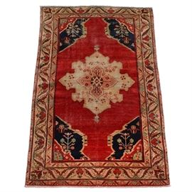 Antique Persian Hand-Knotted Bakshaish Area Rug: An antique Persian hand-knotted wool area rug attributed to the Bakshaish region. It features a floral central medallion with tiny pendants against a bold red lozenge field. To the corners, there are deep blue corner spandrels with floral motifs. Enclosing the field, there is a light peach border with hanging blossoms and lanceolate's. No marks to indicate a manufacturer.