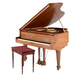 """Vintage Chickering Baby Grand Piano: A vintage Chickering baby grand piano; features include a light mahogany veneer with tapered legs on rolling metal casters, and three foot pedals. Included is a rectangular bench with a loose fitting fabric cover to top, and which opens to storage. The Chickering Company was founded in 1823 in Boston by Jonas Chickering, and remained in operation until 1983. The piano bears a remnant of the Chickering mark to its fallboard, beneath an applied """"Rotstein"""" family name."""