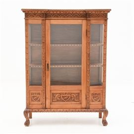 Antique Italian Carved China Cabinet: An antique Italian carved fruit wood china cabinet. This cabinet feature a floral-carved molding above glass panels to the sides and front. Other features include a brass hanging pull, two shelves with carved crescents, carved crest and acanthus motifs, and claw and ball feet. This piece dates to the late 19th or early 20th century.