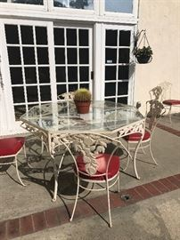 Wrought iron patio set with 6 chairs. Features an apple motif . Red vinyl seats. Very cute!