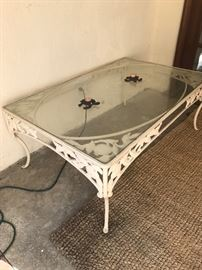 Wrought iron, glass top table-apple motif. Matches patio set