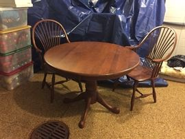 Solid wood table with two chairs.