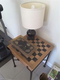 View of Small Table Lamp, Checker Game Board Furniture Table and Small Meditation Lava Rock Decorations.