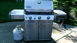 Weber gas grill with side burner, extra tank, and storage underneath