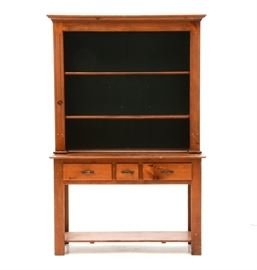 Pine Hutch-on-Table: A maple stained pine hutch-on-table in two sections, to include an upper unit, having a molded cornice, over two shelves with plate groove and a green painted back. The base unit has three drawers and a lower shelf, between straight legs.