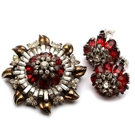 "Mid Century Sterling Pennino Rhinestone Brooch and Earrings: A sterling silver brooch and clip earring set from New York jewelry manufacturer Pennino, known for fine craftsmanship in the Italian tradition. During WWII the firm often made its cocktail style jewelry out of sterling. This set features both colorless and ruby red rhinestones. The brooch is designed in a distinctive tiered pattern with a whorl of leaves and fleurettes along the outer edge. The reverse of each earring is marked ""Pennino, Sterling, Pat. Pend."" while the brooch is marked only ""Pennino Sterling."" The total weight, inclusive of all materials, is 1.630 ozt."